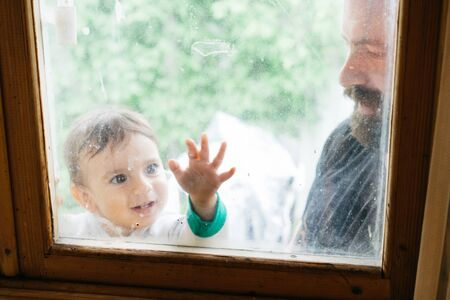 Father and little son are playing together. Dad and child looking through the window. Family weekend together