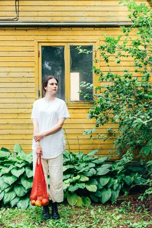 A woman in white trousers and shoes is standing on the front of the yellow wall of a country house with two cotton shopping bags with apples and oranges. Zero waste concept 版權商用圖片