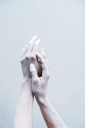 A pair of elegant female hands in dried clay on a white background. Ceramics production. Creativity and hobby concept.