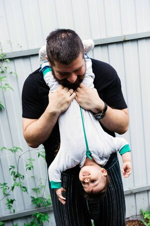 Father and little son are playing together. Dad holds the child by the legs upside down. Family weekend together Stockfoto