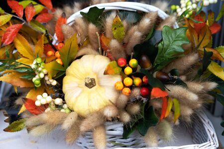 Small pumpkins, heather, beautiful autumn flowers decor for the harvest festival. Fertility and fertility concept