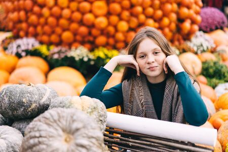 A beautiful red-haired teenage girl with freckles on a pretty little face sits near a cart with pumpkins at the harvesting festival dedicated to the harvest and the end of the summer.