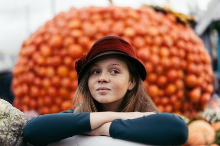 A beautiful red-haired teenage girl in retro hat with freckles on a pretty little face sits near a cart with pumpkins at the harvesting festival dedicated to the harvest and the end of the summer.