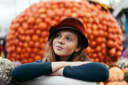 A beautiful red haired teenage girl in retro hat with freckles on a pretty little face sitting near a cart with pumpkins at the harvesting festival. Dedicated to the harvest and the end of the summer Banco de Imagens