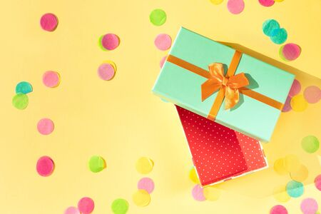 Beautiful festive gift box in trend colors with a green lid, an orange bow neo light. The inner walls of the box are red and white polka dots. Yellow pastel background with multicolored paper confetti