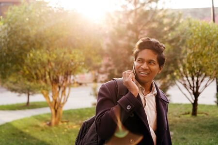 Attractive Indian man in a business suit and coat with a backpack walking on a sunny autumn day in city park and talking on the phone with friend about meeting, looking back, smiling Stock Photo