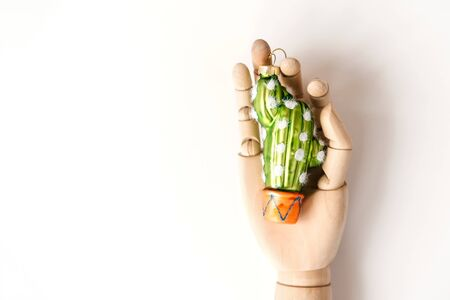 Glass Christmas toy in the shape of a cactus in the mock up of a hand. The concept of New Year preparations and sales. Environmental Protection. Zero waste. Minimalist background. Funny holiday card