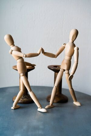 Two wooden human figures standing on a table shake hands. The concept of a positive greeting friends in a cafe at the tables