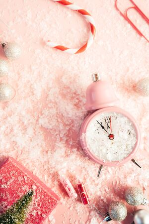Alarm clock, silver Christmas balls, striped cane, gift wrapping, paper clip, Christmas tree on pink covered artificial snow background. Funny composition. Happy holiday layout. New year preparations