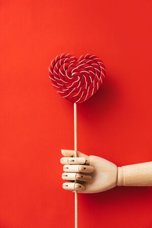 Heart shaped wooden hand holding a large red and white striped lollipop. The concept of Valentines Day, love and friendship. Minimal simple flat lay composition layout. Natural material and light