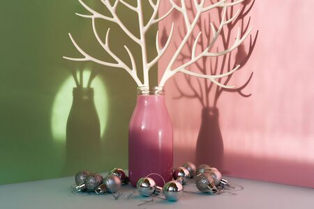 A pink bottle with white plastic branches imitating deer antlers stands on a blue surface with green mint and pink walls around and silver Christmas balls. Creative New year neo composition Stock Photo