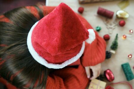 A girl in red pullover and Santa Claus hat slipping on the table with props for Christmas decorating house and the tree on craft paper, clothespins in the shape of hearts for the Advent calendar