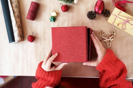 A child hands in red pullover opening red gift box closing. On the table props for decorating house and tree on kraft paper thread, wooden deer head, glitter apple. Creative new year handmade concept