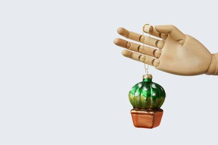 Glass Christmas toy ball in the shape of a cactus holding by dummy a hand. The concept of New Year preparations and sale. Environment Protection. Zero waste. Minimalism background. Funny holiday card Stockfoto