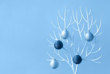 Christmas tree made of white plastic horns and bauble decoration on the deep blue background.