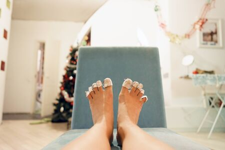 Female legs with toes wrapped in foil on a turquoise armchair against the background of the New Year decorated home cozy interior. Do-it-yourself pedicure at home. Funny christmas concept