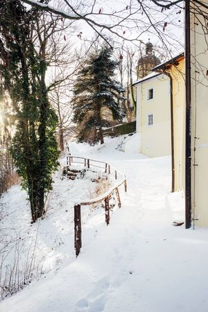 Frosty and Sunny winter day. A path along the pale yellow walls of houses, footprints in the snow. Landscape vertical Banque d'images - 135495735