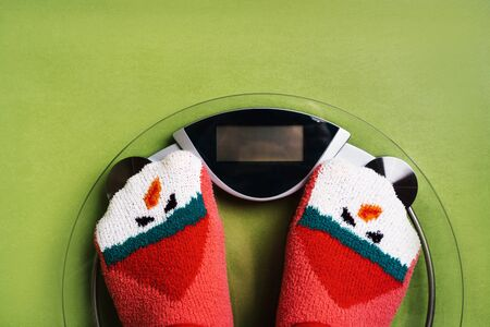 Girl standing on the scales in Christmas fun red green socks with snowman background. The problem of excess weight gained during the holiday New Year. Pre holiday diet. Gluten free food, keto, sweet