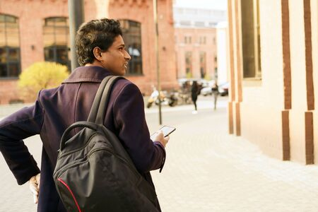 A man in a dark blue jacket and black backpack is standing in city with a phone in his hands looking for navigation. Solo overseas traveler, sightseeing. Taxi booking by mobile app Stockfoto