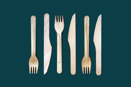 Set of disposable wooden knives and forks on a dark green emerald background. The concept of plastic fre, zero waste, environmental protection. Minimal simple creative layout in trendy color Reklamní fotografie