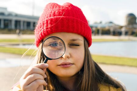 Beautiful blonde teenage girl of 12 years old in a red knitted hat looking through a magnifying glass holding glass in her hand. The concept of exaggeration and distortion of reality at a young age