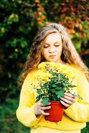 Cheerful smiling teenage girl of 14 years old with long curly red hair in a yellow sweater with flowers in pot on the nature. Summer vacation weekend concept