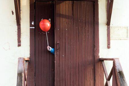 Mano de los niños en una chaqueta azul que sobresale de detrás de una puerta de madera con una bola roja en un palo. Juego de escondite, concepto para niños.