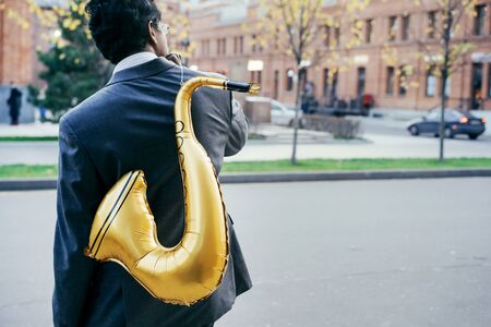 Funny handsome Indian man in a white shirt and business suit with a golden color inflatable tube standing on the street. Fun holiday corporative festive concept. Portrait from the back without a face