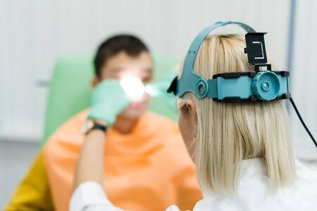 Ispezione preventiva di un adolescente in una struttura medica. Pediatra medico otorinolaringoiatra. Ispezione dei seni nasali con il riflettore della fronte e lo specchio nasale Archivio Fotografico