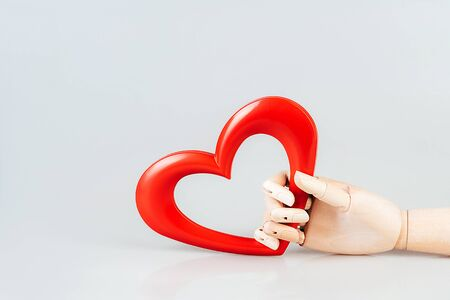Heart shaped in wooden hand on on white background. The concept of Valentines Day, love and friendship. Minimal simple still life composition layout. Natural material and light