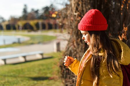 Girl with blond long hair in a knitted red hat and yellow jacket, standing in the park and squinting under the rays of the autumn sun