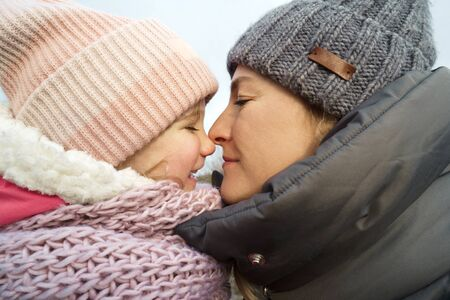 Daughter of four years and mother with warm winter clothes hats and scarves. Close-up portrait in profile. Maternity and childhood concept. Love and care. Outdoor walks in weekend Banco de Imagens