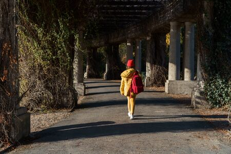 Girl with blond long hair in a knitted red hat and yellow jacket, extending into the distance along the park alley under the rays of the autumn sun. Weekend in the city