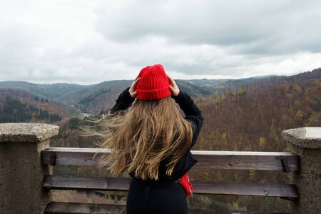 Long-haired girl in a black jacket, a red knitted hat standing on top of a high tower in the mountains. Wind in the hair. Weekend and school travel concept. Faceless