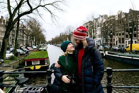 Loving couple man and woman having fun on the streets of Amsterdam in winter warm clothes. Husband embracing wife. Funny moments of life together. Valentine day concept