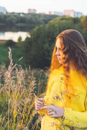Cheerful smiling teenage girl of 14 years old with long curly red hair in a yellow sweater on the nature. Summer vacation weekend concept. Selective focus Stock Photo
