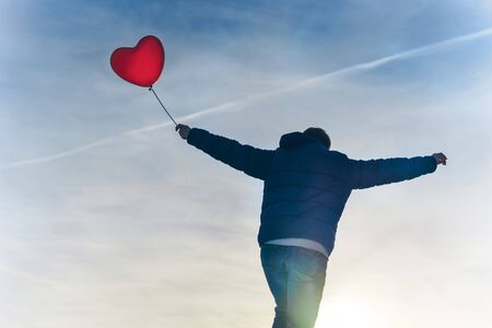 Man from the back in a warm winter jacket of blue color and jeans with a red heart air rubber balloon in hand against the blue sky on a frosty day. T-shaped silhouette symbolizing freedom and flight Stockfoto
