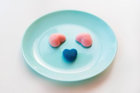 Marmalade and jelly candies sugar hearts blue and pink. Funny muzzle on a turquoise plate. Valentines classic Day Party Concept. Treats mint for guest children holiday birthday. Edible kids fun Stockfoto
