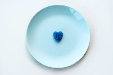 Blue lonely marmalade sugar heart on a light pastel blue turquoise mint plate. Valentines Day classic Party Neo Concept. Treats for guests on children birthday. One heart is unwanted