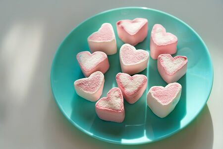 Heart shaped pink marshmallow lying on a blue turquoise plate. Valentines Day Party Concept. Treats guest children holiday birthday. Vertical banner social network and mobile phone screen