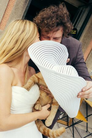 Loving wedding couple long-haired blonde and curly man sitting in a cafe on the street with a red cat, hiding behind a large white hat. Fun Wedding Walking Concept. Happy holiday celebration.