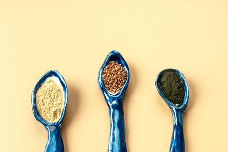 Three blue ceramic clay handmade spoons with flax seeds, chlorella powder, matcha and maca for making classic drink. Daily doses of natural organic ingredients for womens health and beauty. Flatlay