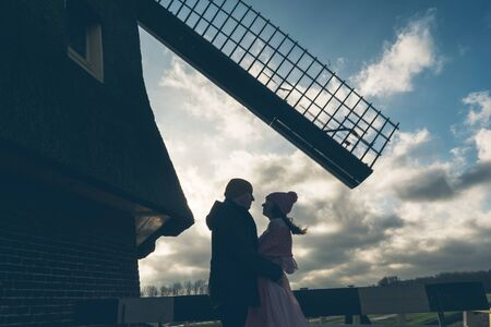 Loving couple man and woman face to face looking into each others eyes the background of the mill. Rural spring landscape. Family Relations and Valentines Day Concept Stock Photo