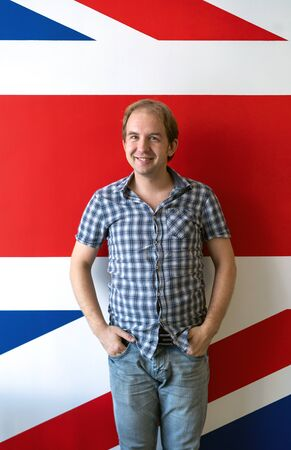 Cheerful man in a plaid shirt with short sleeves on the background of the wall with the image of the British flag. English teacher at a language school.