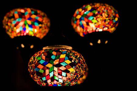 Turkish oval lanterns from small multi-colored piece of glass hanging in the dark on a black background. Concept of Islamic holiday Ramadan, Muslim Eid al-Adha. Kurban Bayram post