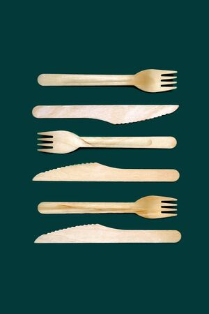 Set of disposable wooden knives and forks on a dark green emerald background. The concept of plastic fre, zero waste, environmental protection. Minimal simple creative layout in trendy color