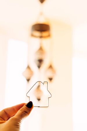 A cookie cutter in the shape of a house in a female hand against the background of a Turkish chandelier. The warmth of the hearth. Mortgage repayment concept. Cozy house Stockfoto
