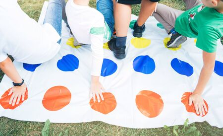 Children play a twister on the grass. Hands on red. Team game outdoor Stockfoto