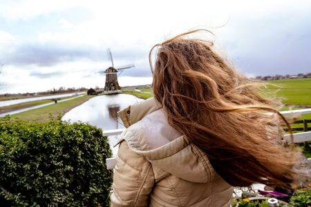 Girl with long red hair developing in the wind. Woman looking into the distance at a typical Dutch provincial landscape with a mill and a canal dividing the fields Stockfoto