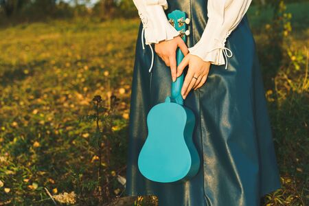 Close-up portrait young woman in a turquoise skirt and a white shirt with blue ukulele in her hands. Yellow-green fall foliage background. Summertime